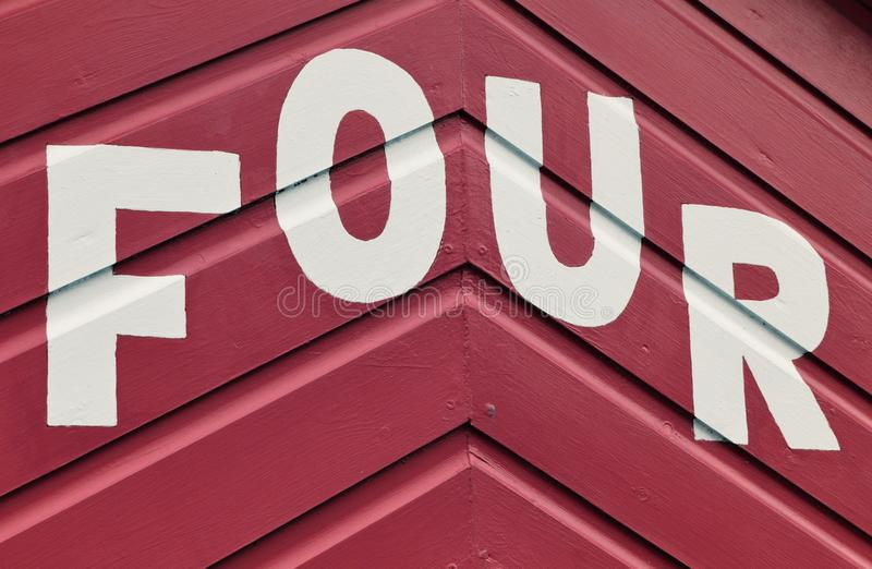 Number FOUR in letters written on the side of a wooden beach hut. The number FOUR in white capital lettering written on the side of a red wooden beach hut royalty free stock photo