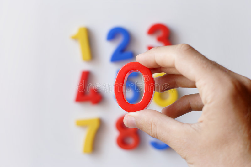 Number fridge magnets. Displaying 1 - 9, hand in focus holding 0 royalty free stock image