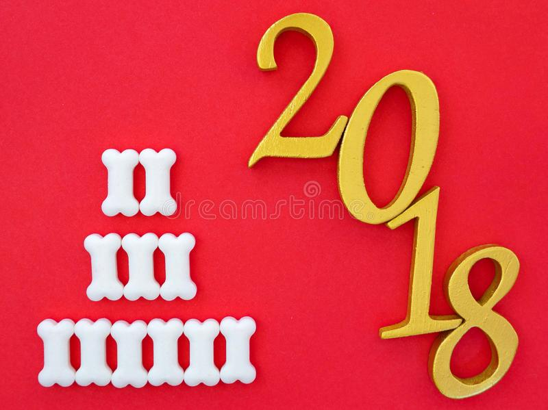 Number 2018 in gold. An image of number 2018 in gold with white bone shape dog treats on bright red paper background, symbolizing auspicious year 2018, Year of royalty free stock image
