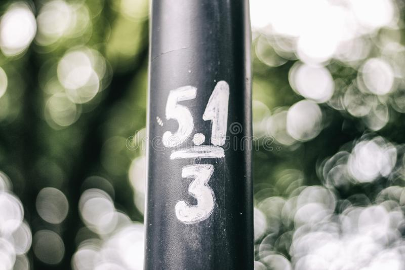 Number 5.1/3 lamp with bokeh. Minimalistic photo. Lamp with signs. White bokeh. Simple composition with circles and lines royalty free stock photography