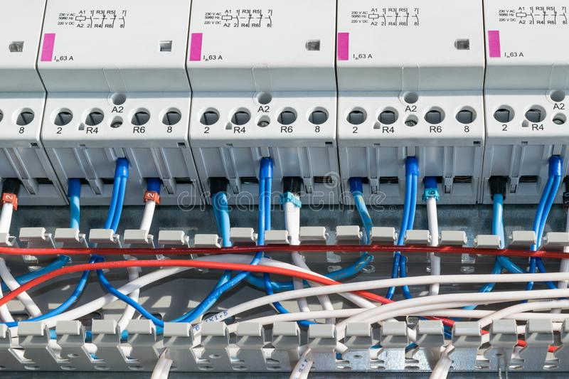 A number of modular contactors, cable channel and wire. Wire laid in the cable channel and connected to the modular contactors in electrical Cabinet. The wires royalty free stock photo