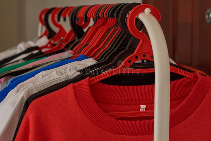Number of multi-colored T-shirts and jackets weighs on hangers stock photo