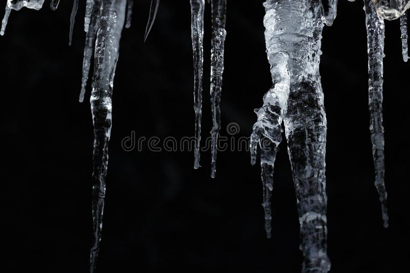 Number of natural icicles on a black background. frozen water in winter. a group of dangling icicles. copy space. stock photos