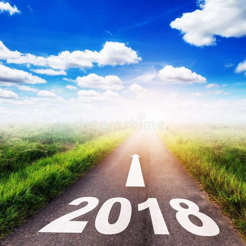 Number of 2018 for New Year concept on country road, field and b. Lue sky with white clouds royalty free stock photos