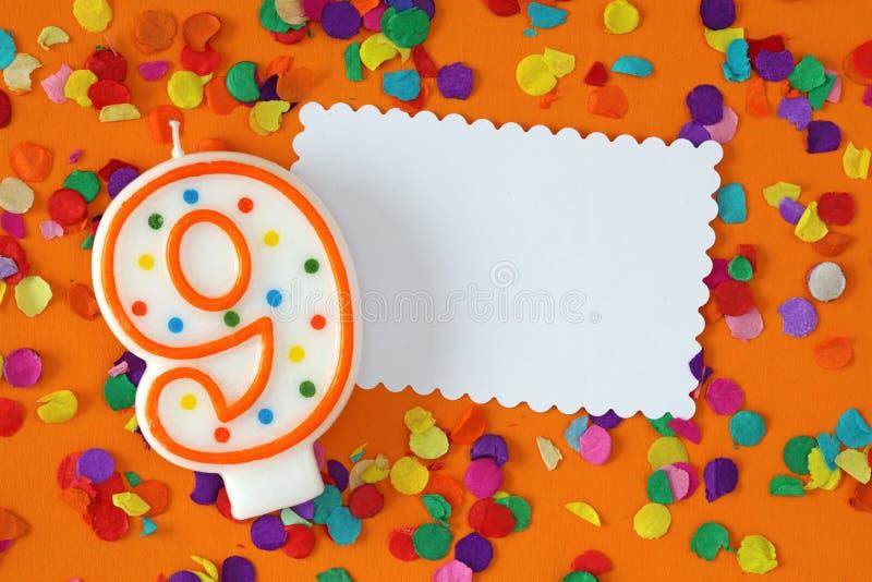 Number nine birthday candle. On orange background royalty free stock images