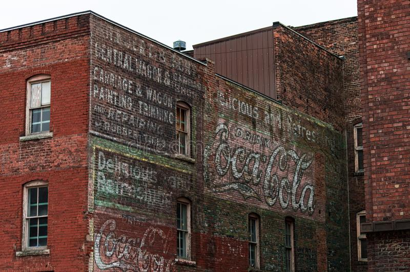Fading advertisments on the side of a brick building Burlington Iowa. A number of old ads and paints along with growing vines on a brick building in a very old