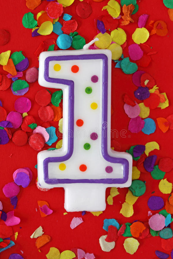 Number one birthday candle. On red background stock images
