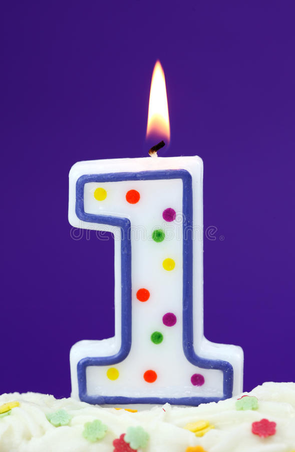 Number one birthday candle. On lilac background stock photo