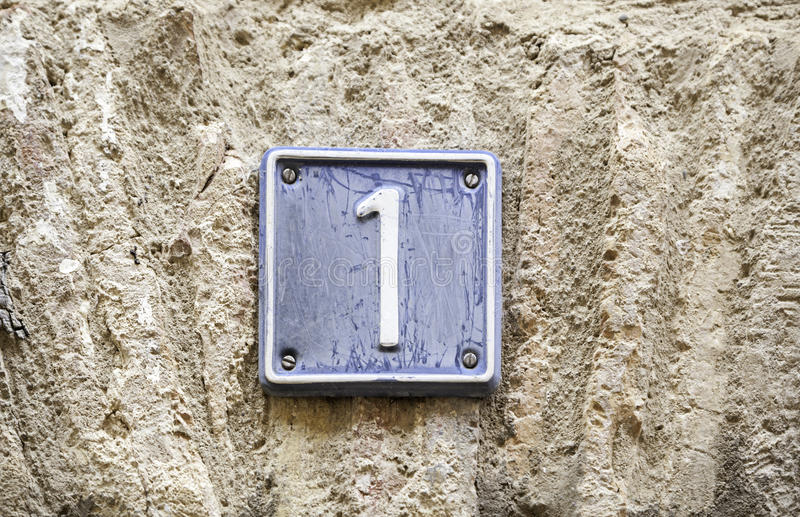 Number one. Details of a  on a wall in the city, signal and information royalty free stock photo