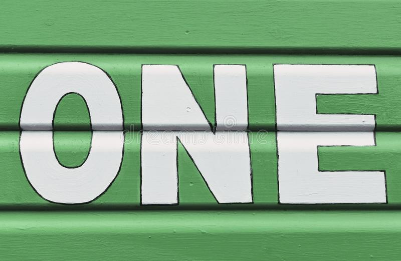Number ONE in letters written on the side of a wooden beach hut. The number ONE in white capital lettering written on the side of a green wooden beach hut royalty free stock image