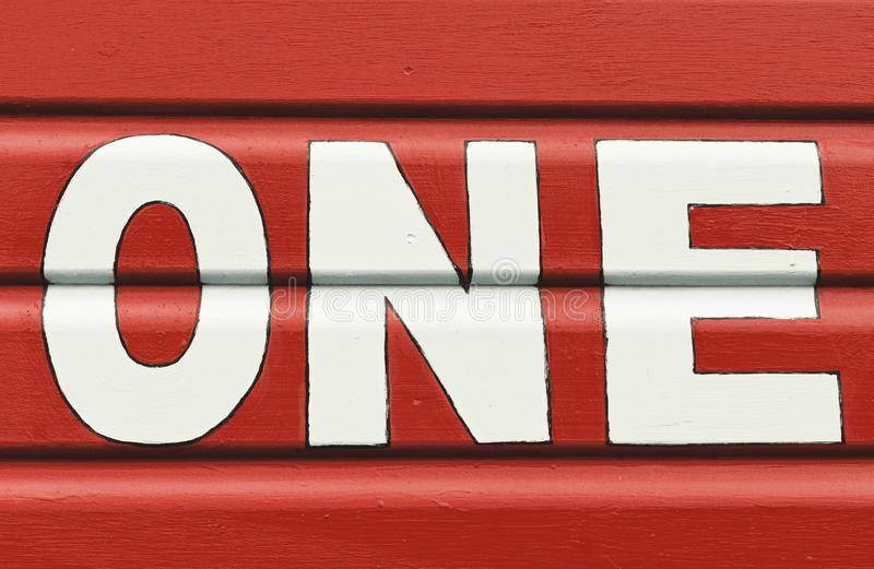 Number ONE in letters written on the side of a wooden beach hut. The number ONE in white capital lettering written on the side of a red wooden beach hut royalty free stock image
