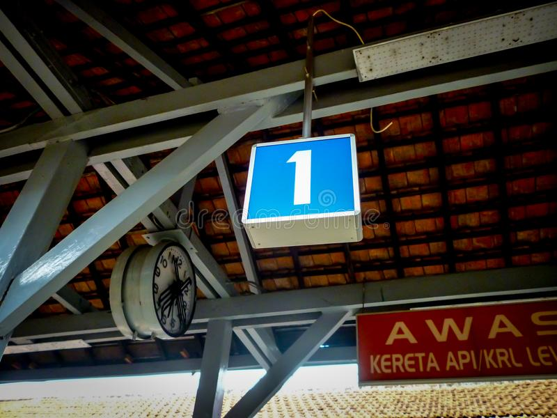 number one sign hanging near a big clock to indicate railway platform number with a board saying caution train passage royalty free stock images