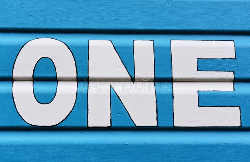 Number ONE in letters written on the side of a wooden beach hut. The number ONE in white capital lettering written on the side of a blue wooden beach hut stock photo