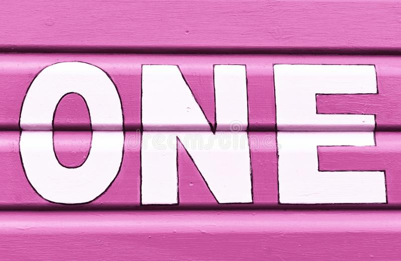 Number ONE in letters written on the side of a wooden beach hut. The number ONE in white capital lettering written on the side of a pink wooden beach hut royalty free stock image