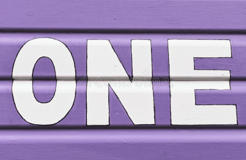 Number ONE in letters written on the side of a wooden beach hut. The number ONE in white capital lettering written on the side of a purple wooden beach hut stock image