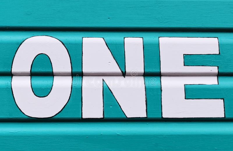 Number ONE in letters written on the side of a wooden beach hut. The number ONE in white capital lettering written on the side of a turquoise wooden beach hut royalty free stock image