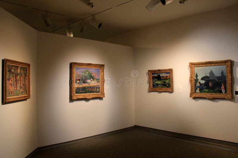 Number of paintings on walls in one of many rooms, Memorial Art Gallery, Rochester NY, 2017. Number of paintings framed in gold, set on walls of room under soft royalty free stock photo