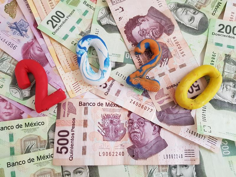 number 2020 in plasticine colors, on mexican banknotes of various denominations royalty free stock photography