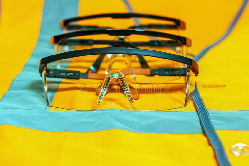 A number of protective glasses on an orange waistcoat with reflective strips. stock images