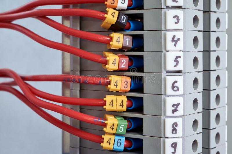 A number of red electrical wires are connected to the through terminals royalty free stock image