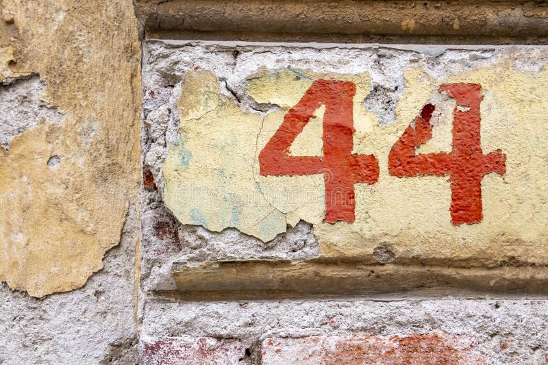 Number 44 in red peeling paint on an old brick building wall with cracked plaster royalty free stock photos