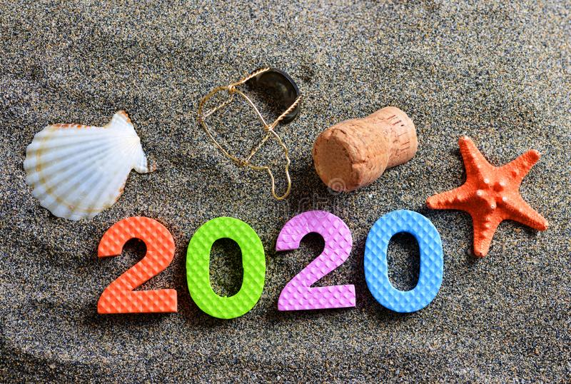 Number 2020, sea shell, starfish and cork stopper of champagne on the sand beach. Happy New Year and summer holiday concept royalty free stock photo