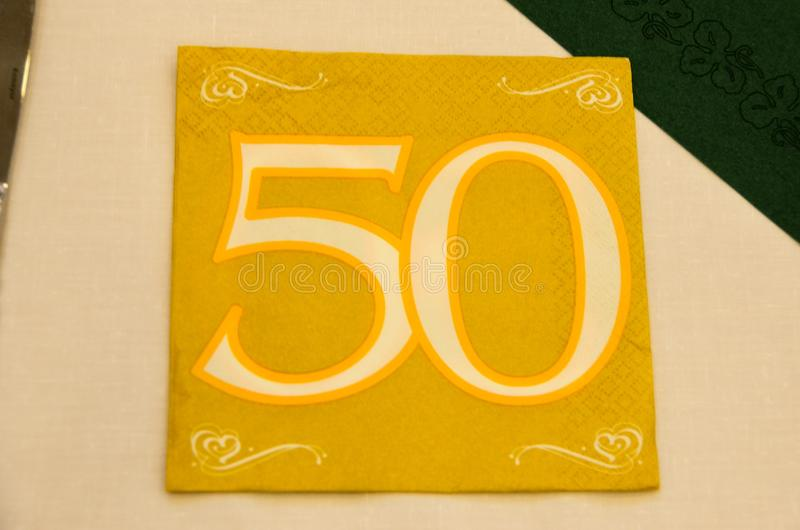 Number 50 on a serviette. The number fifty on a golden serviette stock photography