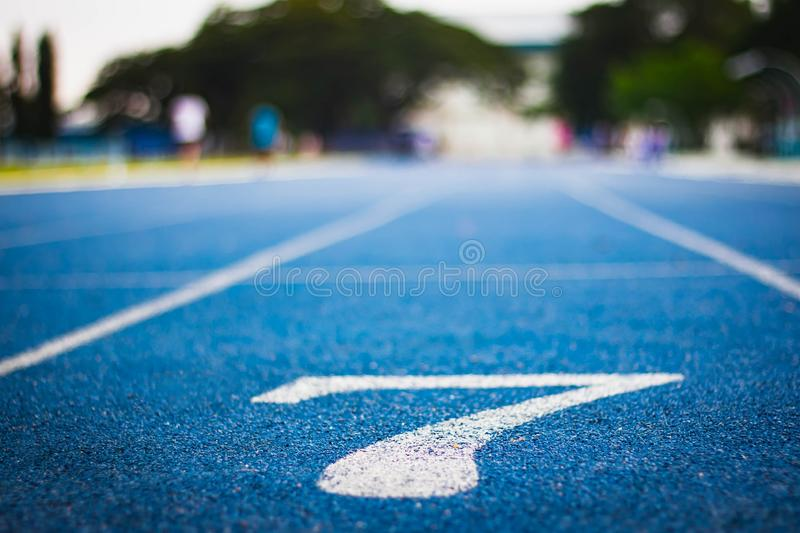 Number seven on the start of a running track .Blue treadmill with different numbers and white lines.Selective focus on Number. Blured background. Close up stock photos