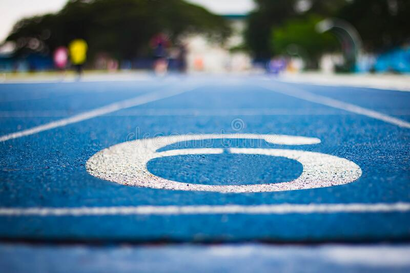 Number six on the start of a running track .Blue treadmill with different numbers and white lines.Selective focus on Number. Blured background. Close up stock image
