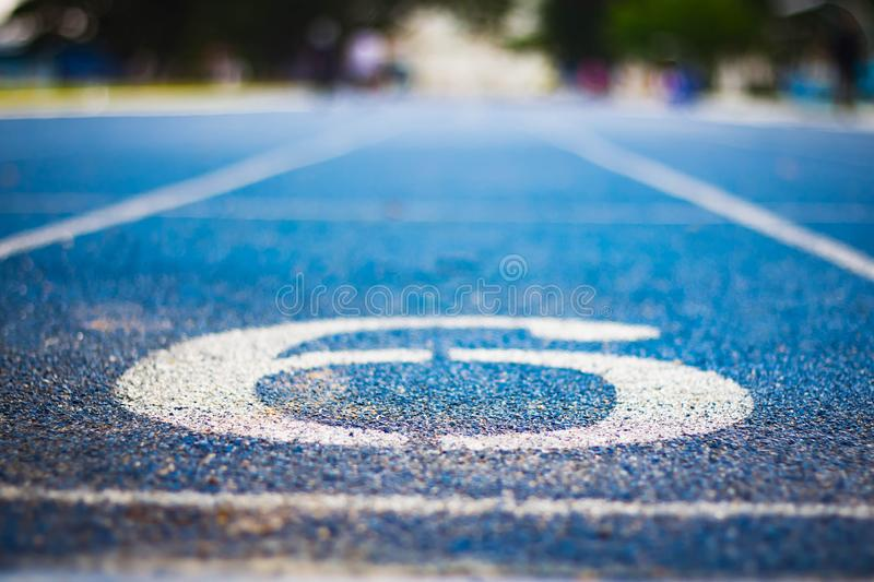 Number six on the start of a running track .Blue treadmill with different numbers and white lines.Selective focus on Number. Blured background. Close up royalty free stock photography
