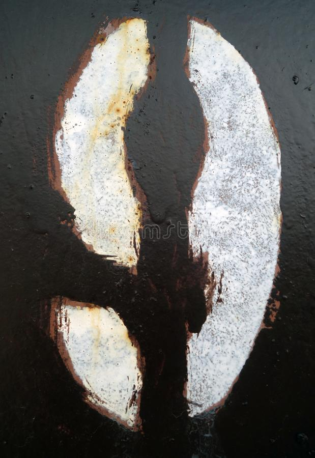 Number 9 in stencil on dark brown metal wall stock photography