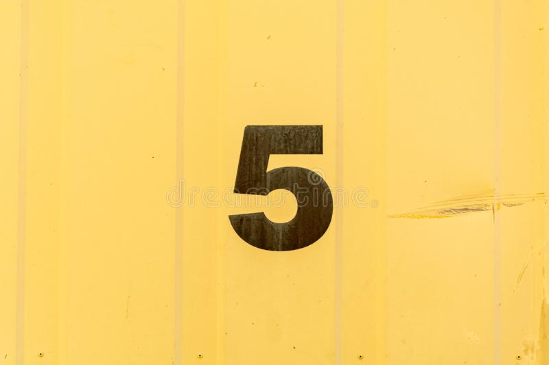 Number 5 stencilled in black on yellow background. Number 5 stencilled and painted in black on a yellow background with copy space placed in the center of the royalty free stock images