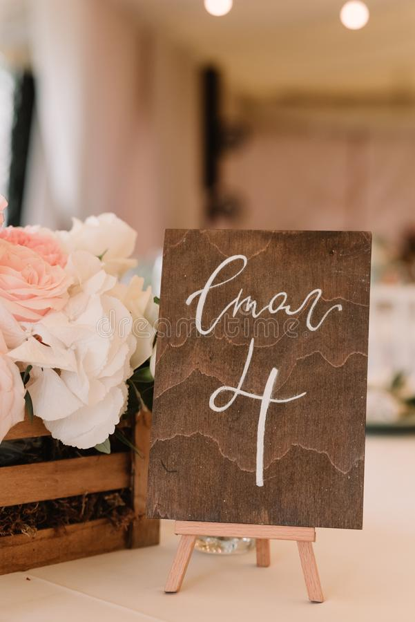 Number of a table on the wooden plate. Detail of a modern stylish wedding. stock photos