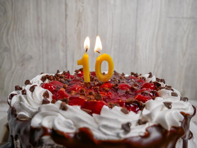 Number ten candle lit on top of a chocolate cherry cake royalty free stock image