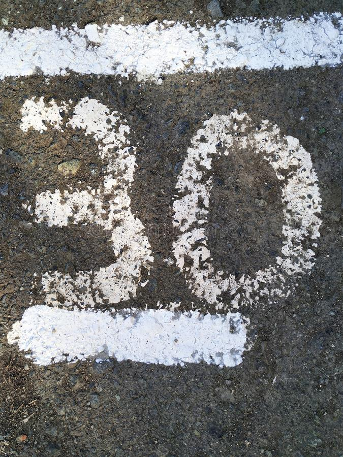 The number thirty written in white paint on the gray asphalt. The bottom is underlined by a straight line, the top is a horizontal stock photography