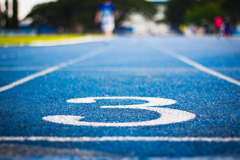 Number three on the start of a running track .Blue treadmill with different numbers and white lines.Selective focus on Number. Blured background. Close up royalty free stock image