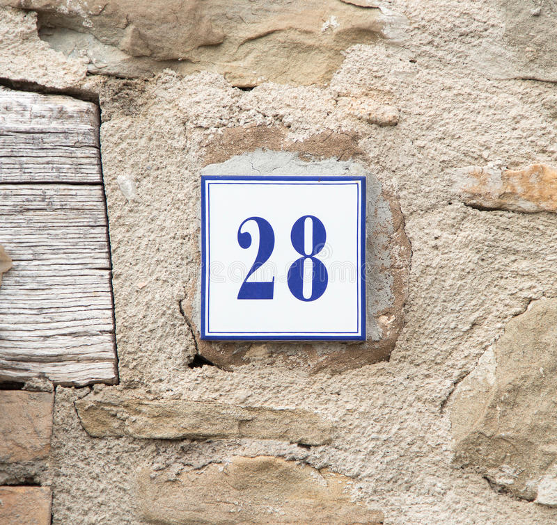 Number twenty eight on the grey stone wall. Ceramic number twenty eight on the grey stone wall royalty free stock photography