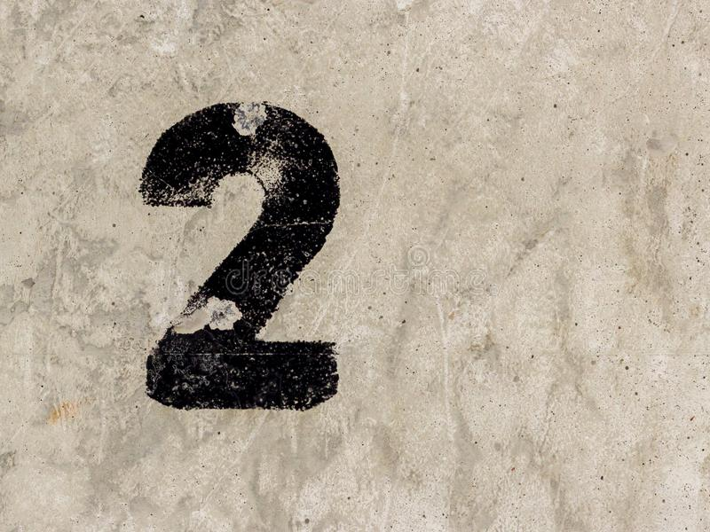 Number two 2 on concrete wall background. Number two 2 black painted on old rugged light grey concrete wall background stock image