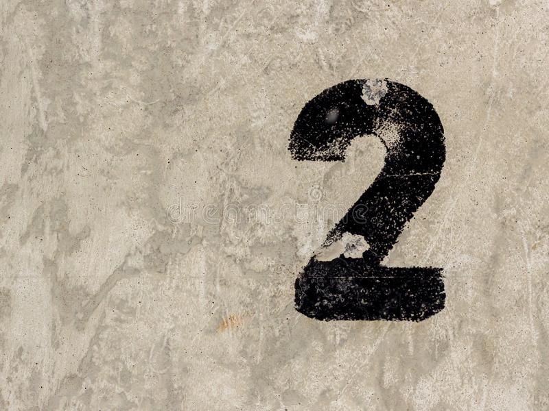 Number two 2 on concrete wall background. Number two 2 black painted on old rugged light grey concrete wall background stock photography