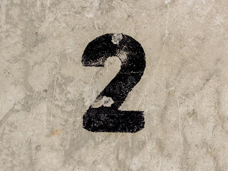 Number two 2 on concrete wall background. Number two 2 black painted on old rugged light grey concrete wall background royalty free stock images