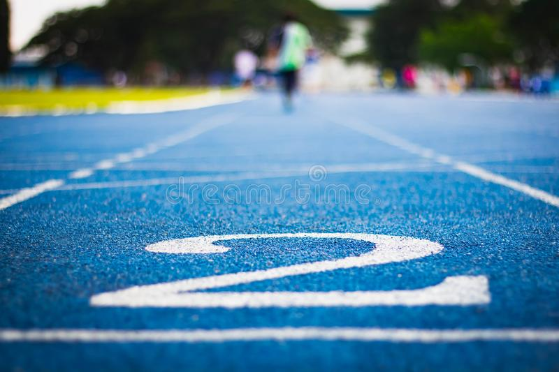 Number two on the start of a running track .Blue treadmill with different numbers and white lines.Selective focus on Number. Blured background. Close up royalty free stock images