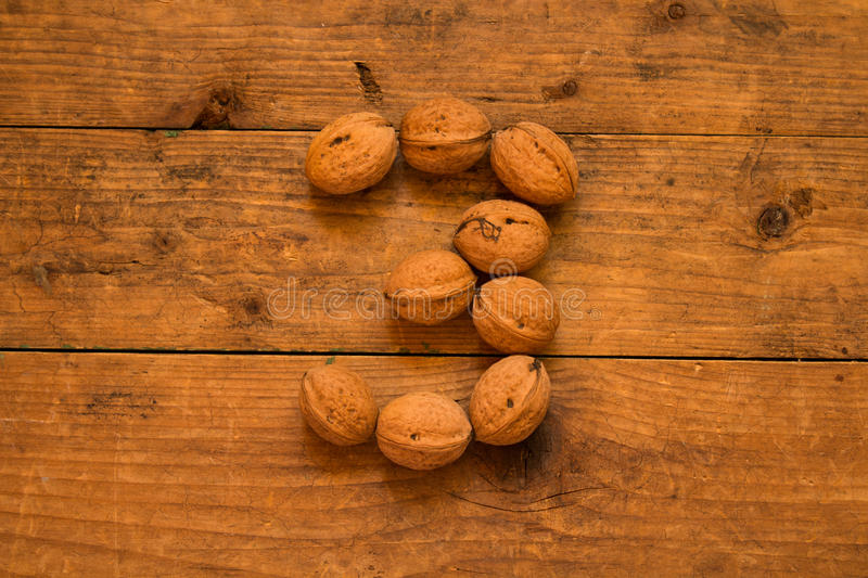Number 3 from walnuts. Top view of english alphabet made from walnuts on a wooden table. Number 3 stock image