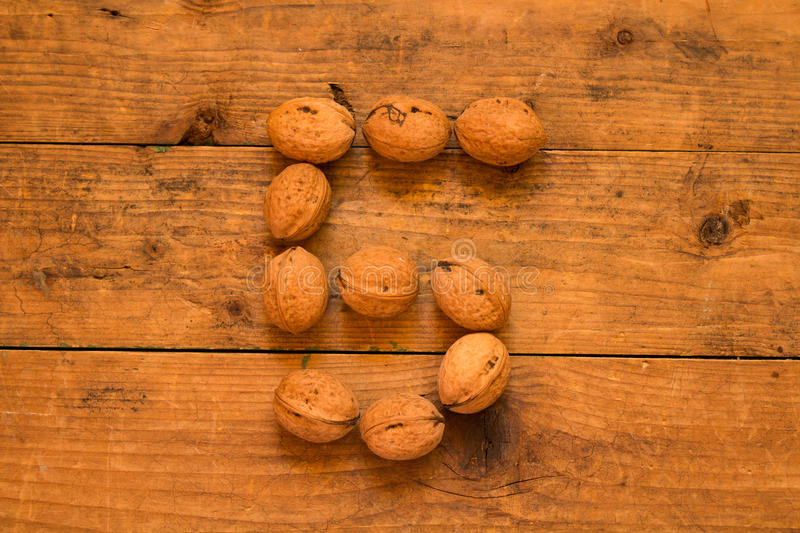 Number 5 from walnuts. Top view of english alphabet made from walnuts on a wooden table. Number 5 stock photography