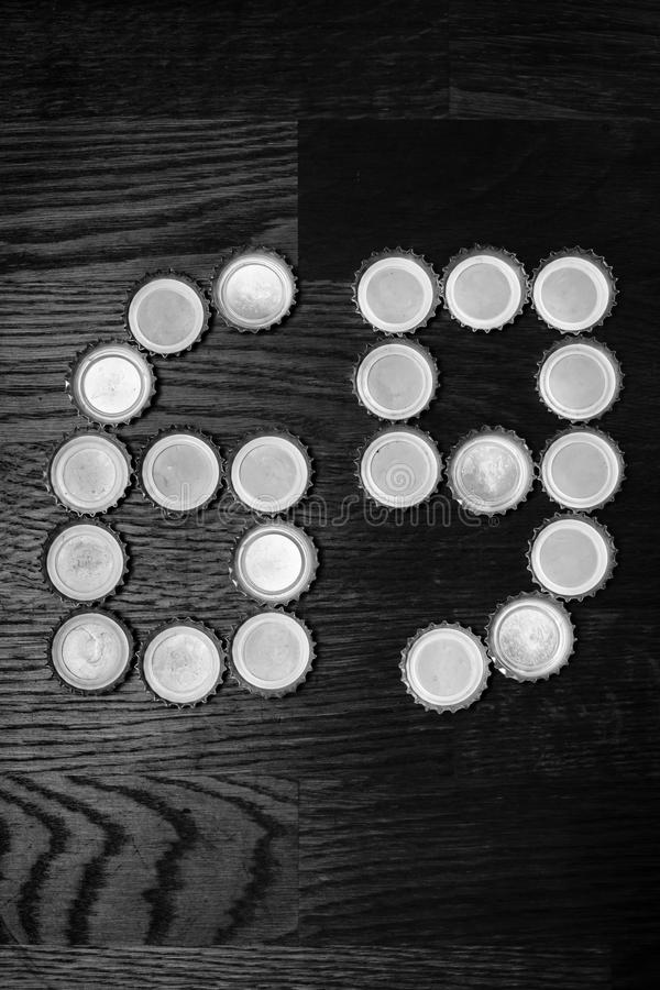 The number 69. On a wooden table laid out of beer caps. Black and white royalty free stock images