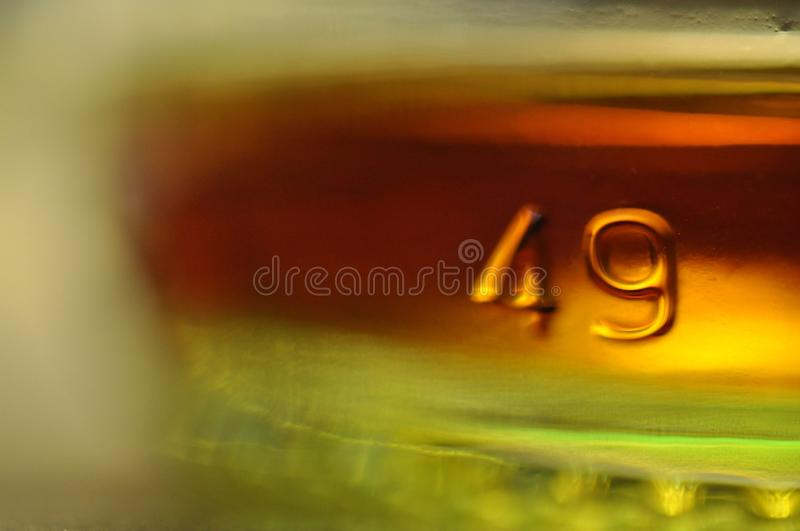 Dregs in a whiskey bottle. The number & x22;49& x22; is stamped into the base of a bottle. Selective focus suggests drunkenness royalty free stock images