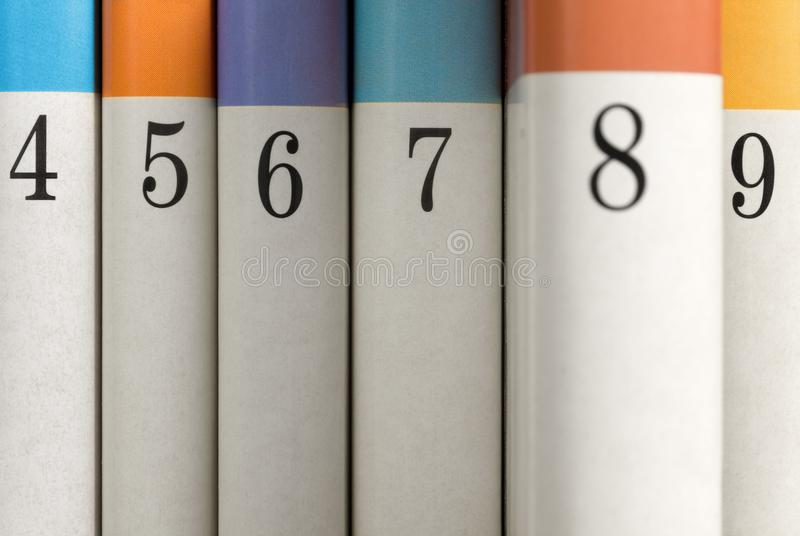Numbered Books in a Row. Six colored numbered books with book number eight partially pulled out from the row stock image