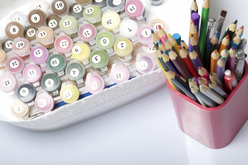 Numbered containers with paints and brushes of different sizes. For drawing by numbers. In a container on a white background. Next stock images