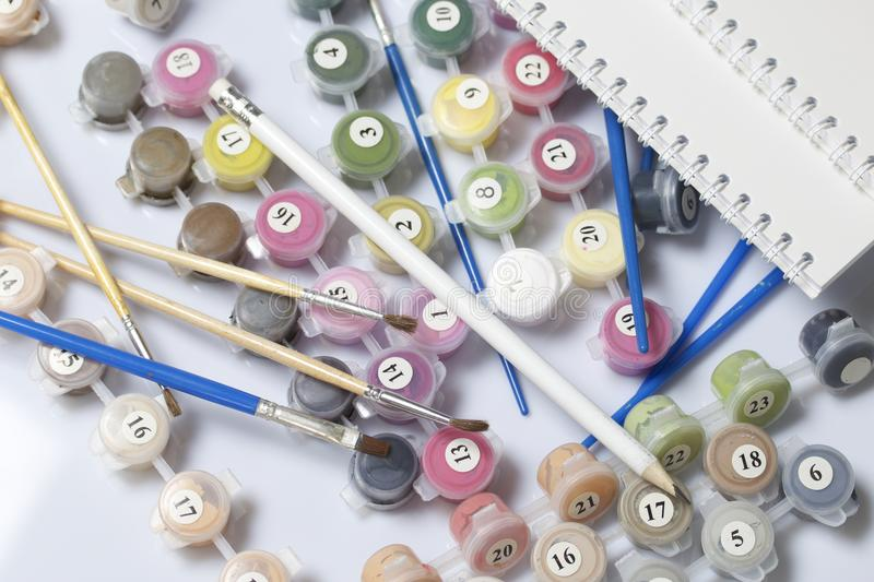 Numbered containers with paints and brushes of different sizes. For drawing by numbers. Notepad and pencil for sketches. Spilled o stock image