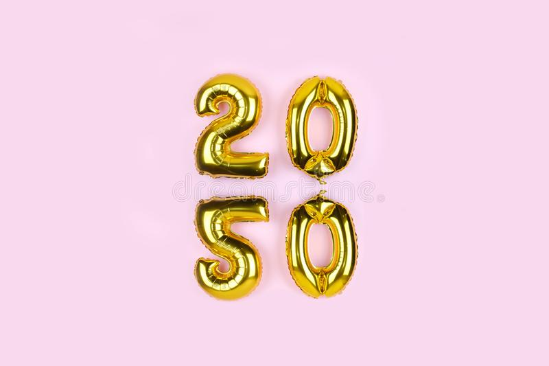 2020 numbers golden foil balloons mirror reflection on pink background. New year holiday party decoration. Metallic air balloons stock image
