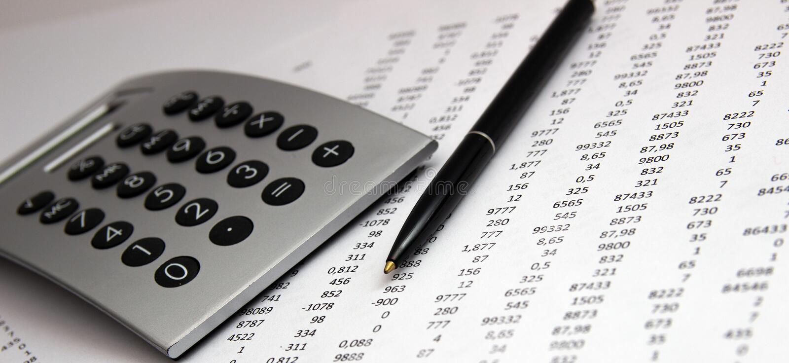 Numbers on paper, a pen and a calculator stock image